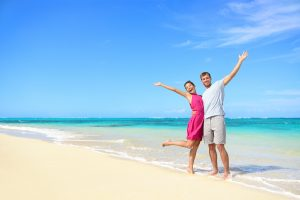 Freedom on beach vacation - happy carefree winning couple with arms up showing happiness and fun on paradise beach with perfect pristine turquoise water in sunny tropical getaway